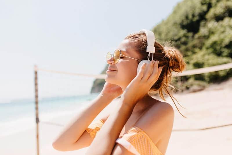 glückliche Frau, die Musik am Strand hört