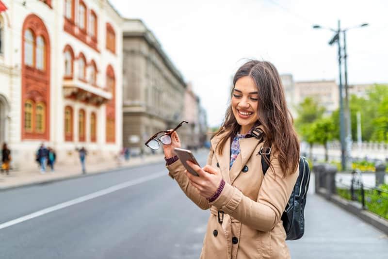 glückliche Frau, die Telefon ansieht