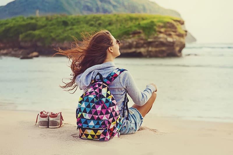 glückliche Frau, die am Strand sitzt