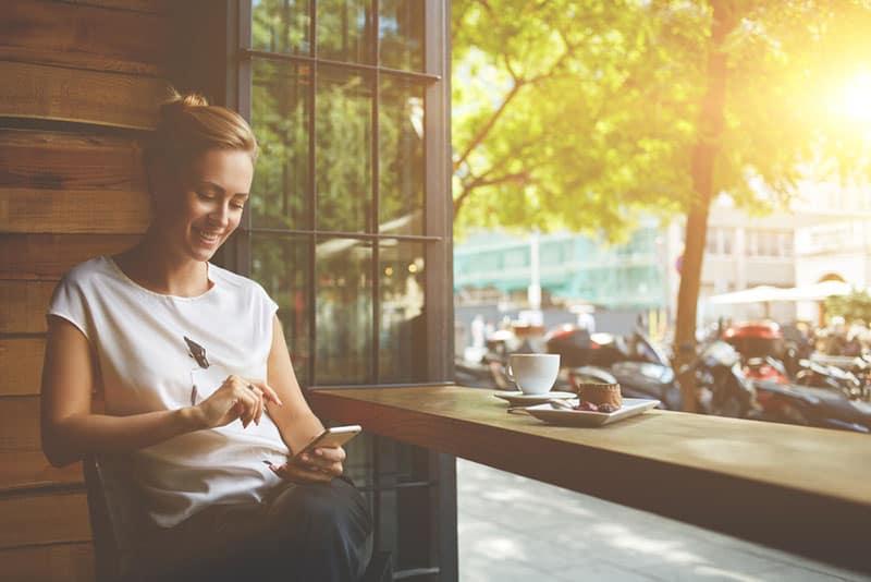 glückliche Frau, die am Telefon im Café tippt