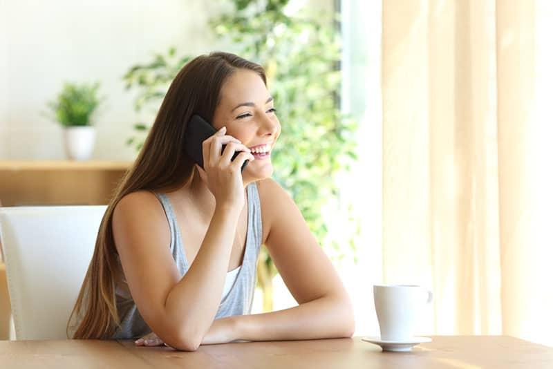 glückliche Frau, die am Telefon spricht
