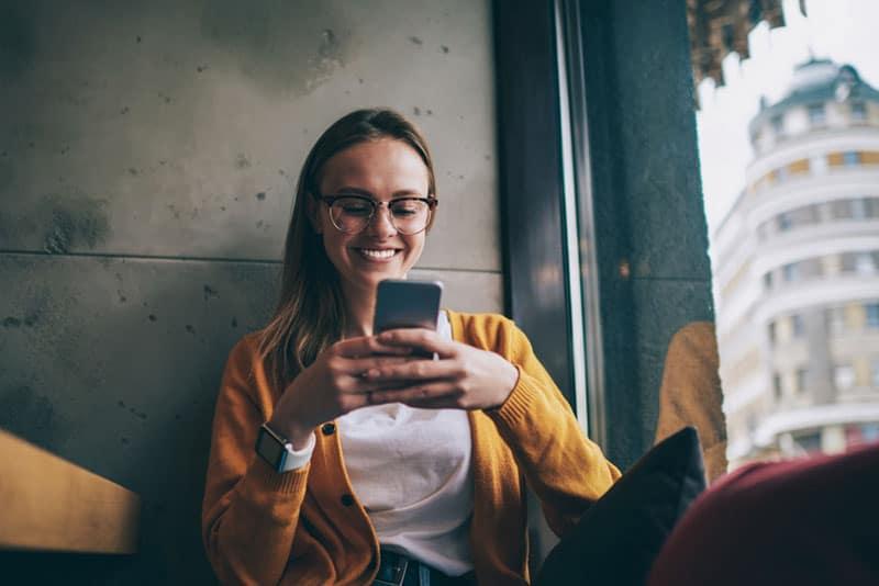 glückliche Frau, die am Telefon tippt