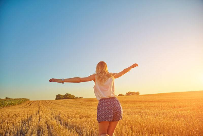 glückliche Frau, die auf Feldsonnenuntergang geht