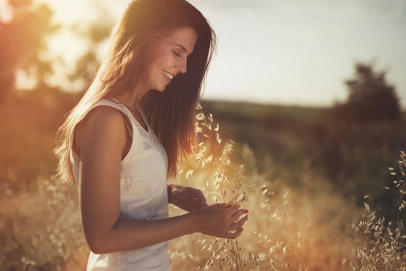 glückliche Frau, die auf dem Feld steht