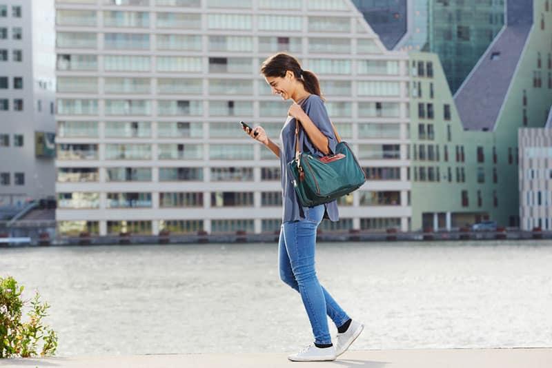 glückliche Frau, die die Straße entlang geht