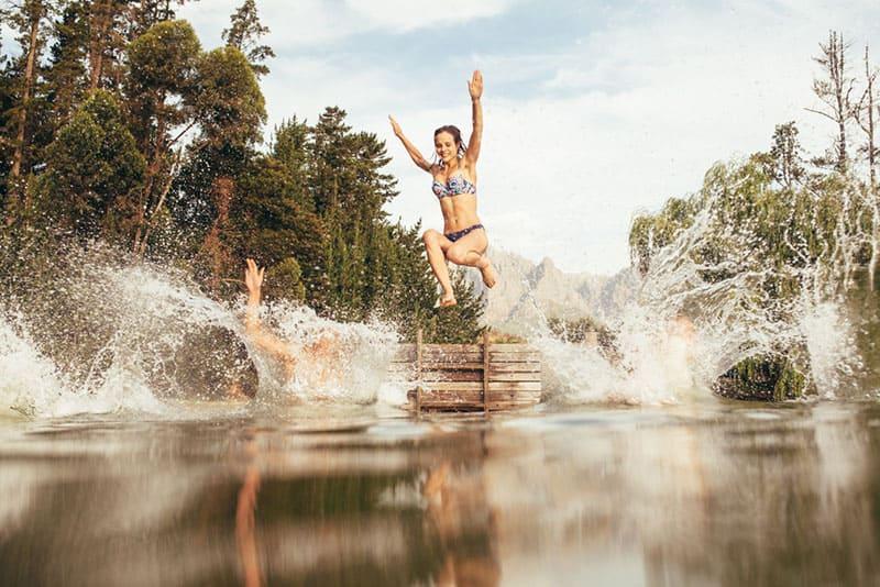 glückliche Frau, die in den See springt