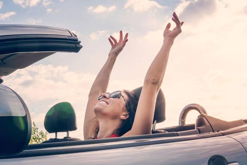 glückliche Frau im Auto lächelnd