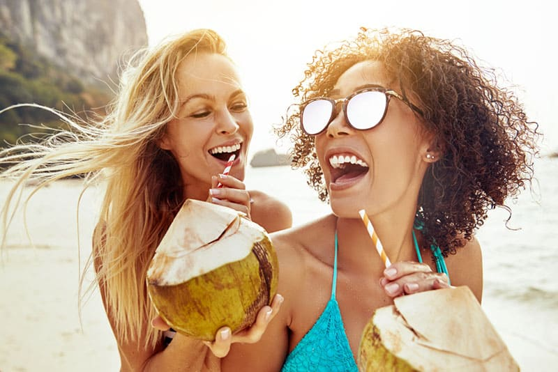 glückliche Frauen, die Kokosnuss am Strand trinken