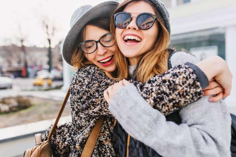 glückliche Freundinnen, die sich draußen umarmen