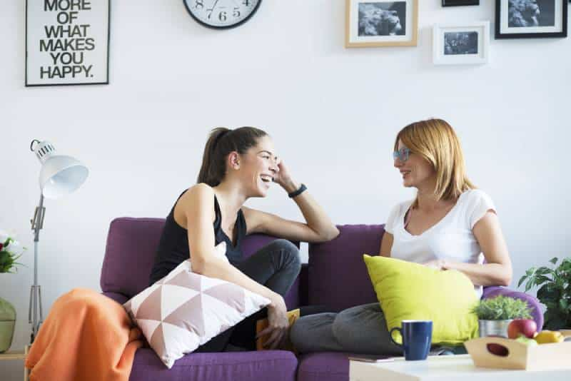 glückliche Freundinnen, die sich im Wohnzimmer unterhalten
