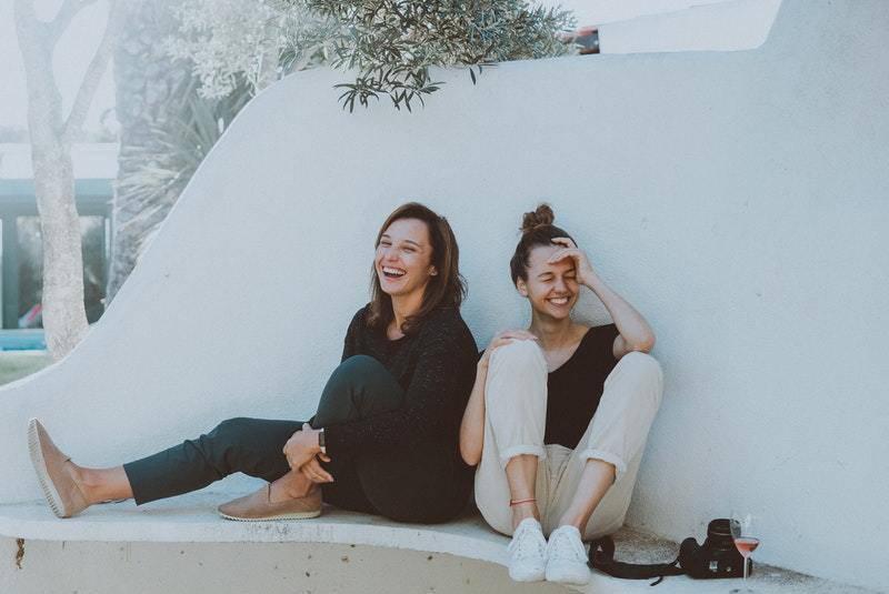 glückliche Freundinnen sitzen draußen