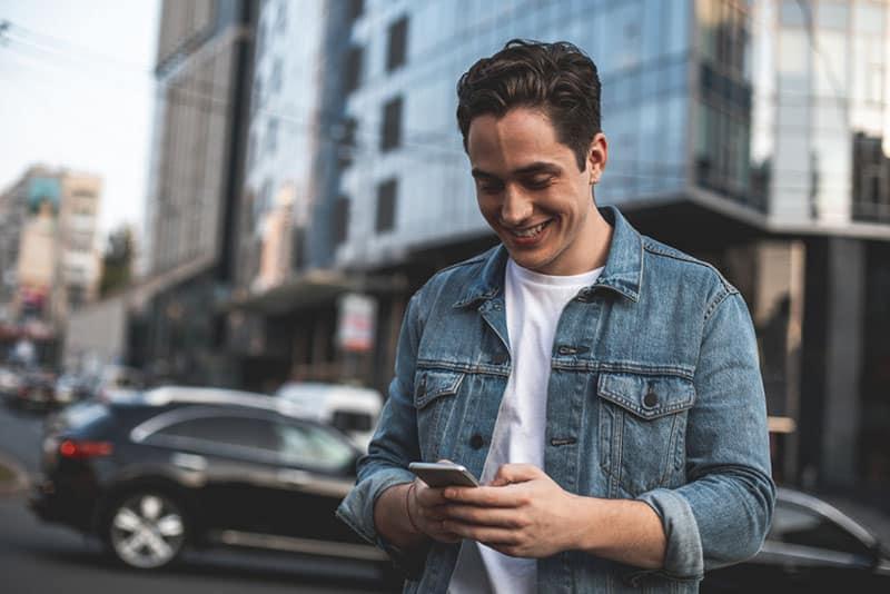 glücklicher Mann, der am Telefon eine SMS sendet