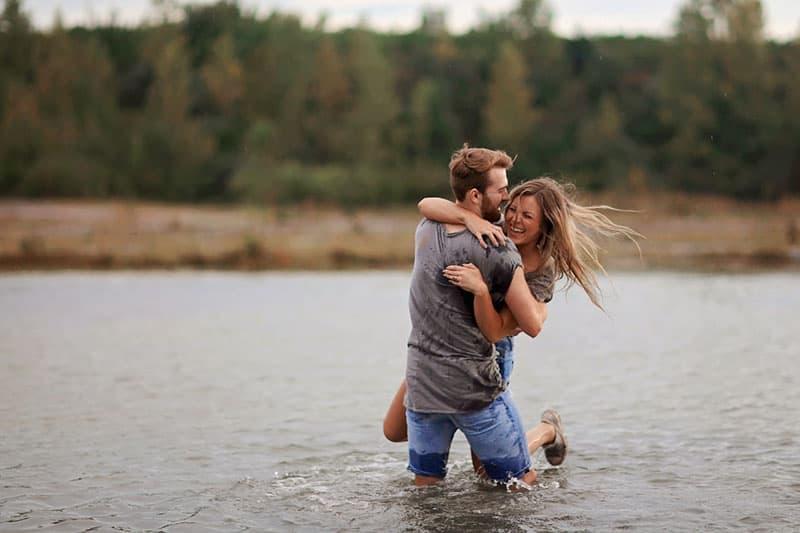 glücklicher Mann, der sein Mädchen im Fluss hält