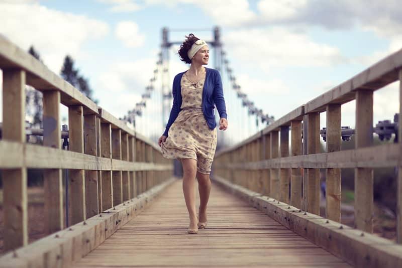 glückliches Mädchen, das über die Brücke geht