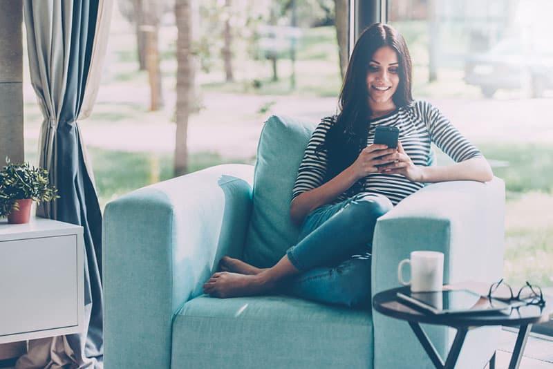 glückliches Mädchen, das auf Sofa sitzt und am Telefon tippt