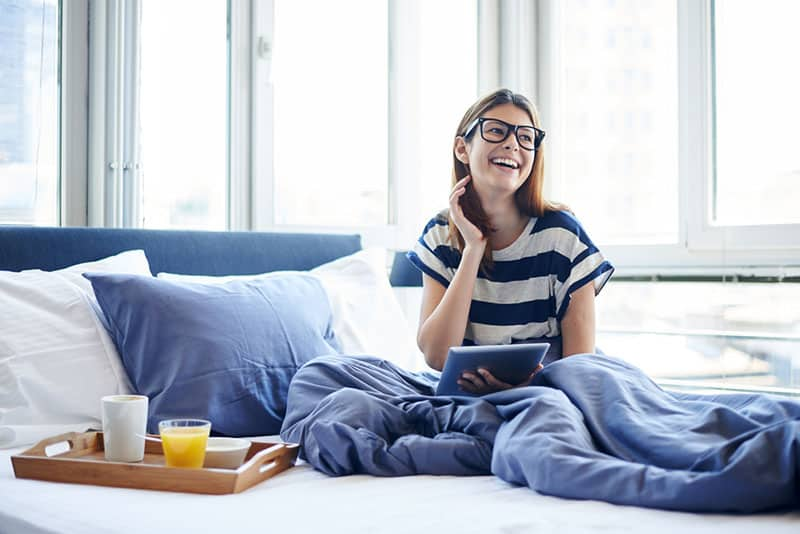glückliches Mädchen, das auf der Couch mit Laptop liegt
