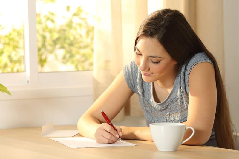glückliches Mädchen, das einen Brief schreibt