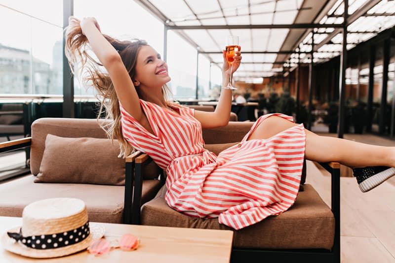 glückliches Mädchen im Kleid, das ein Getränk trinkt
