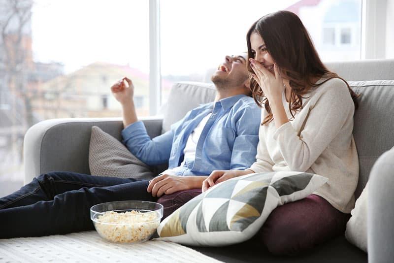glückliches Paar, das Popcorns auf der Couch isst
