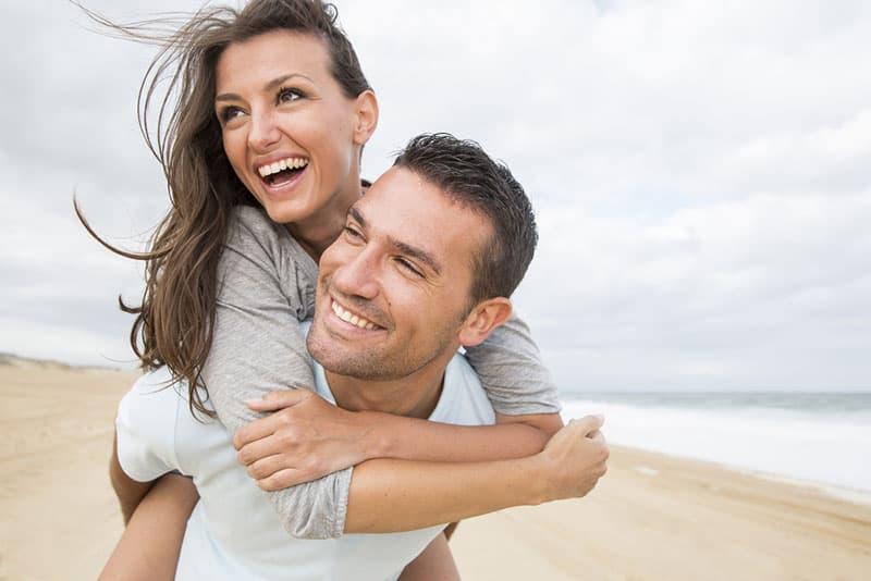 glückliches Paar das am Strand lächelt