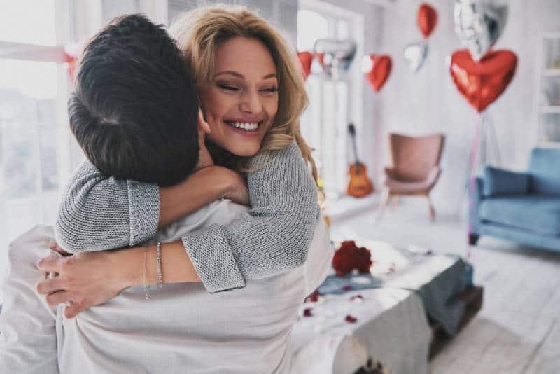 glückliches Paar, das auf Bett umarmt