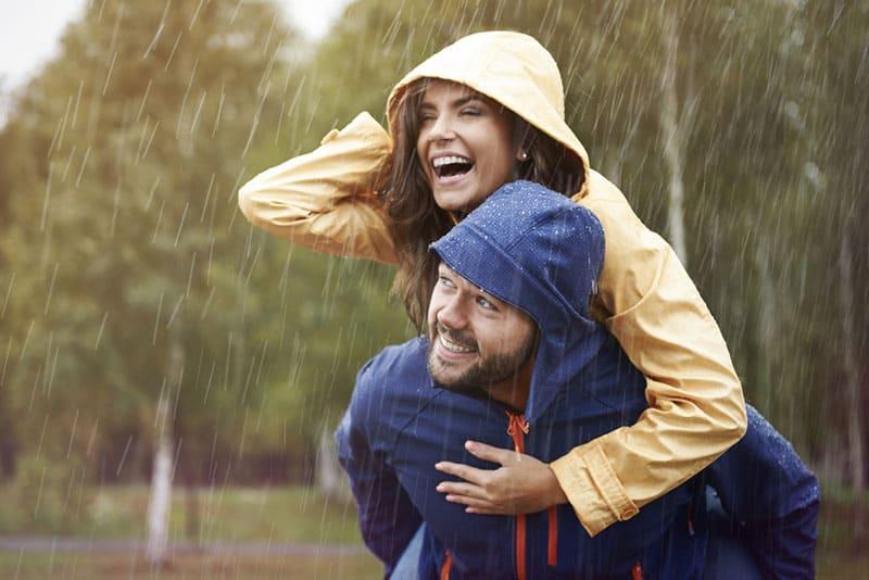 glückliches Paar, das auf dem Regen lächelt