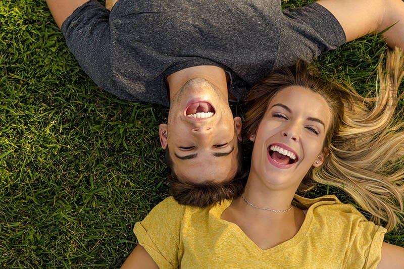 glückliches Paar, das draußen auf Gras liegt