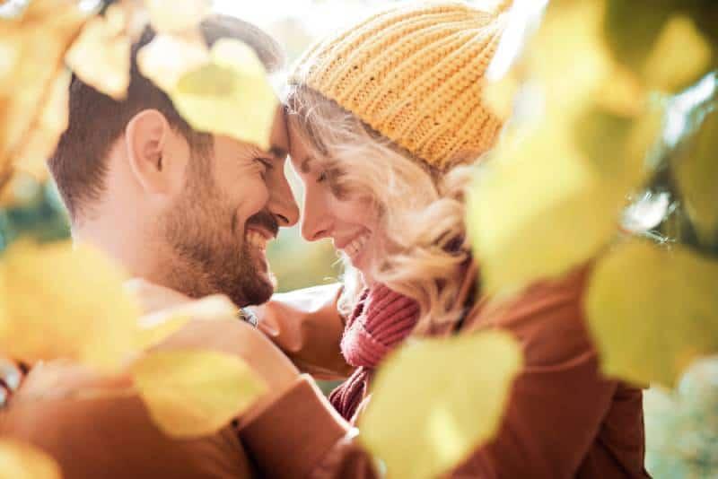 glückliches Paar, das draußen im Herbst umarmt