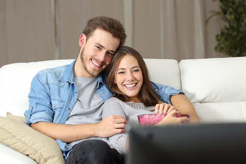 glückliches Paar, das einen Film im Wohnzimmer sieht