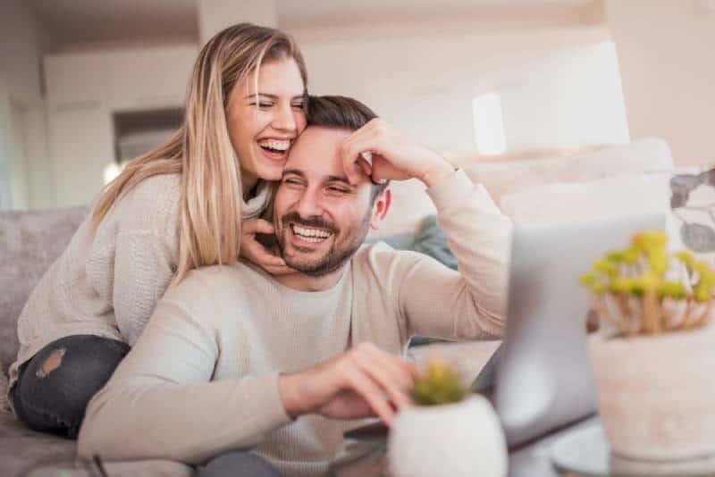 glückliches Paar im Wohnzimmer lächelnd