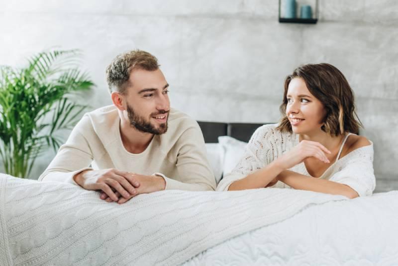 glückliches Paar spricht und liegt auf dem Bett