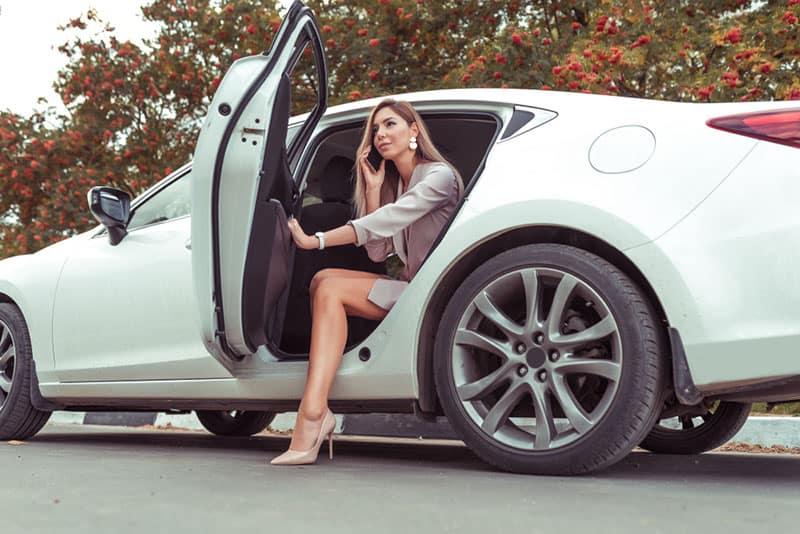 hübsche Frau aus einem Auto aussteigen