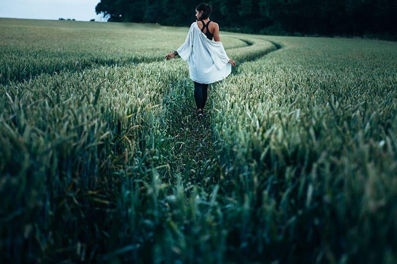 junge Frau, die auf dem Feld geht