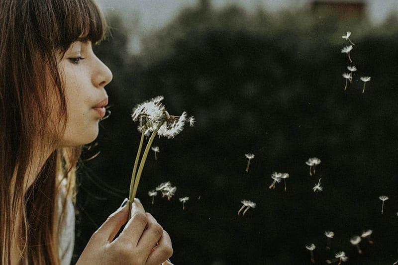 junge Frau, die die Blume bläst