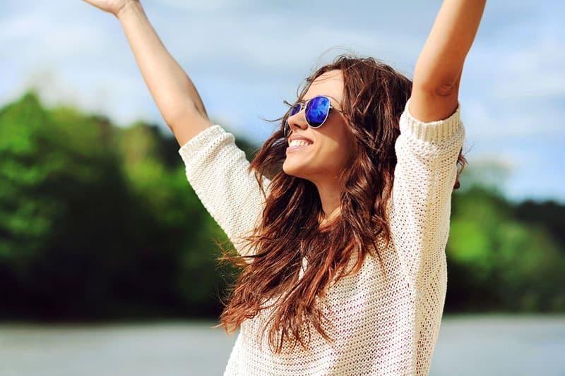 junge Frau mit Sonnenbrille, die Arme ausbreitet