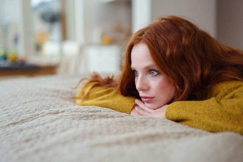 junge Frauen, die auf ihrem Bett liegen, nachdenken und sich ausruhen