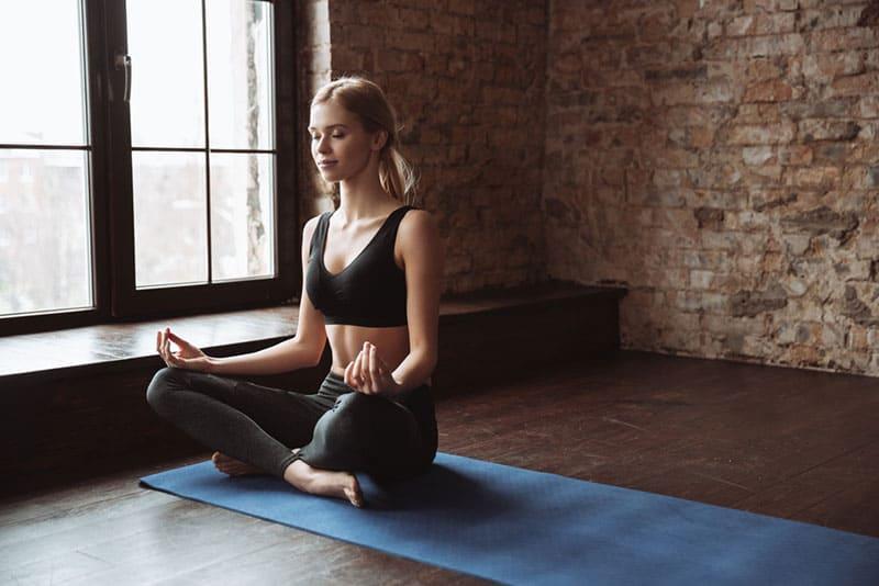 junge blonde Frau meditiert auf dem Boden
