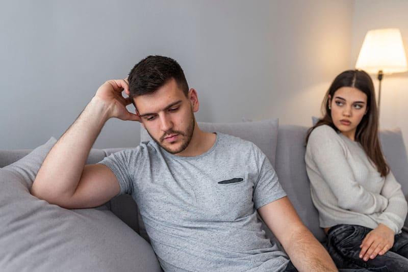 junger Mann mit Freundin die im Wohnzimmer sitzt