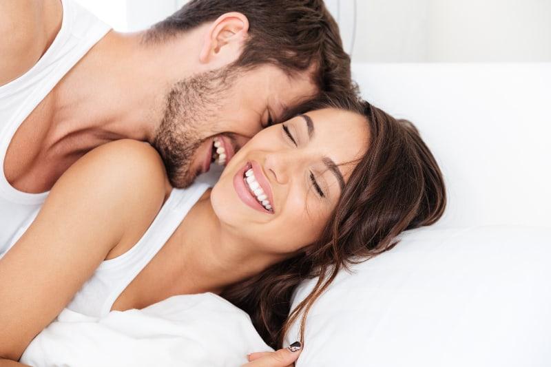 junges Paar lächelt auf dem Bett