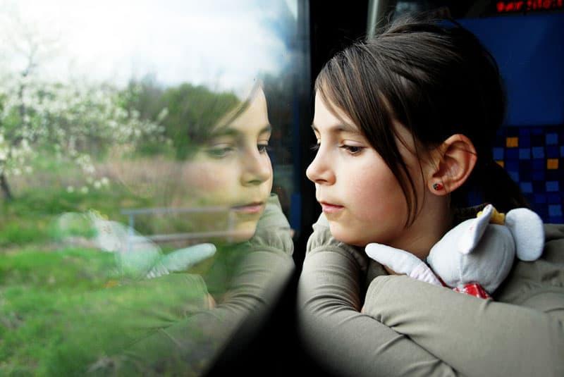 kleines Mädchen, das durch das Fenster schaut
