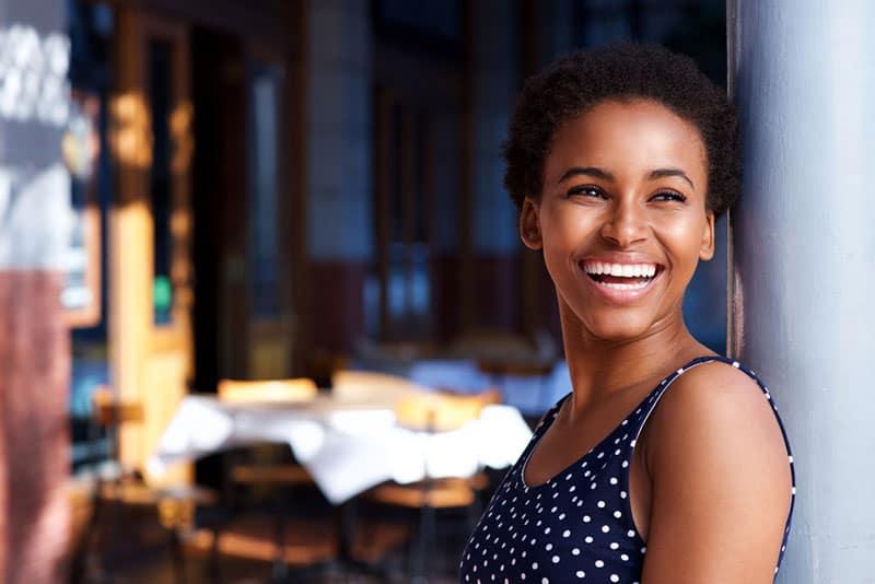 lächelnde Afro-Frau, die an der Tür steht