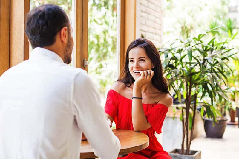 lächelnde Frau im roten Kleid, das Mann ansieht