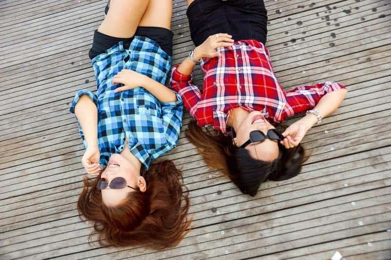 lächelnde Freundinnen, die auf Holzboden liegen