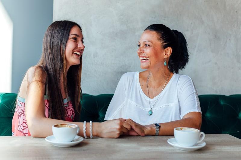 lächelnde Mutter und Tochter im Café