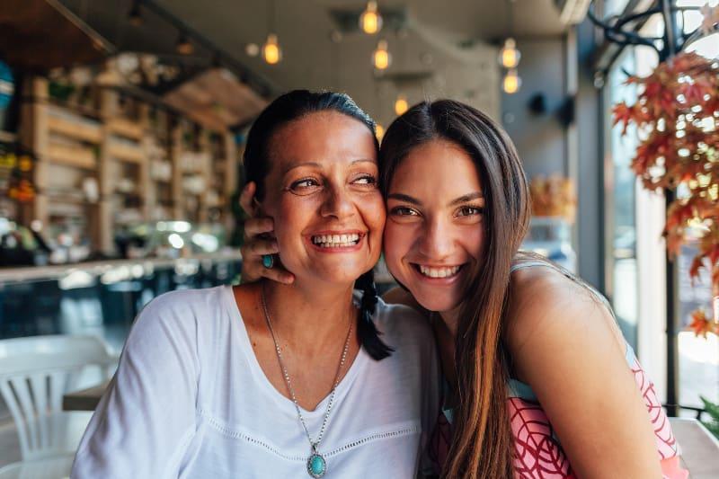 lächelnde Mutter und Tochter im Cafe