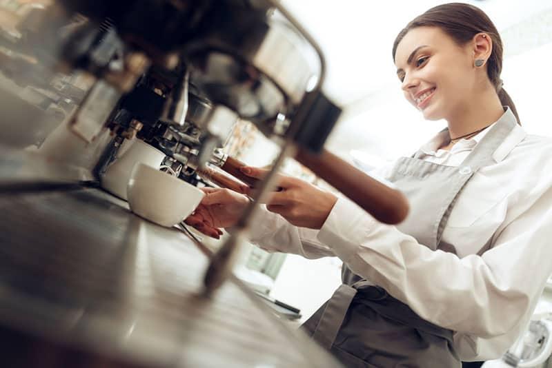 lächelndes Mädchen, das einen Kaffee macht