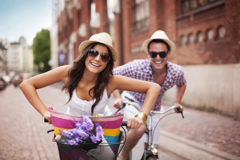 lächelndes Paar, das auf der Straße radelt