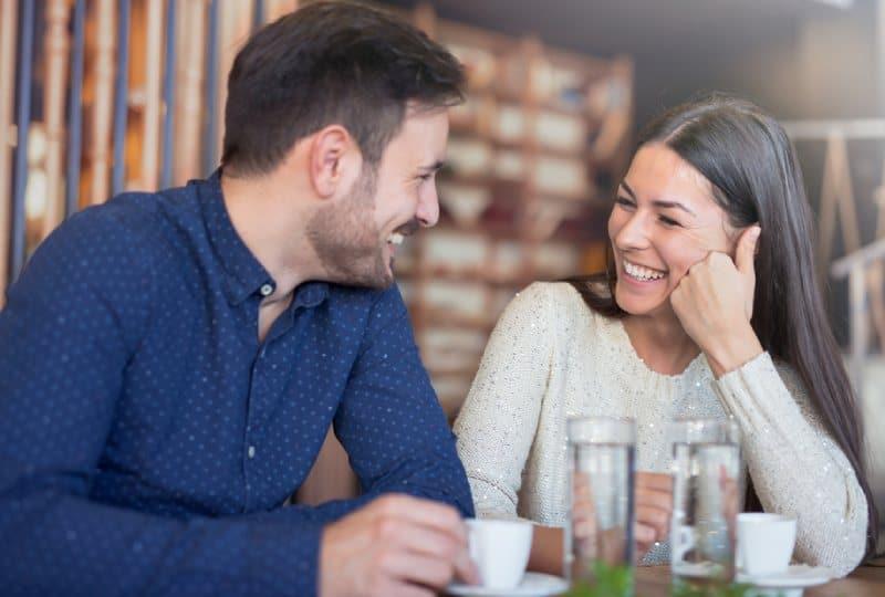 lächelndes Paar, das im Kaffee im Café genießt