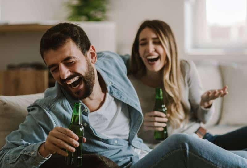 lachendes Paar sitzt im Wohnzimmer und trinkt Bier