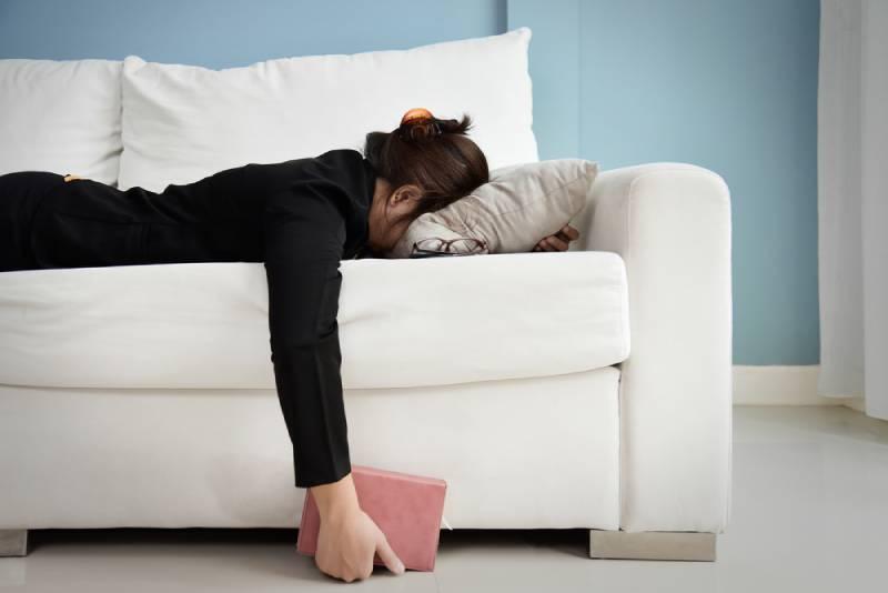 müdes Mädchen, das auf Sofa mit Kopf auf Kissen liegt